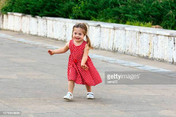 Beautiful little girl with red dress playing