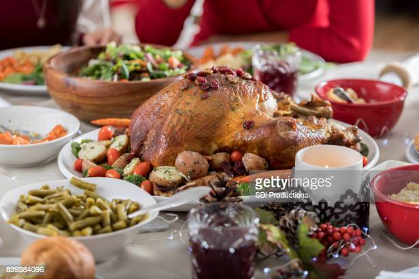 beautiful loaded christmas dinner table with candle and decorations - full stock pictures, royalty-free photos & images