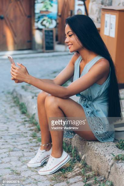 Beautiful long haired girl using smart phone on street