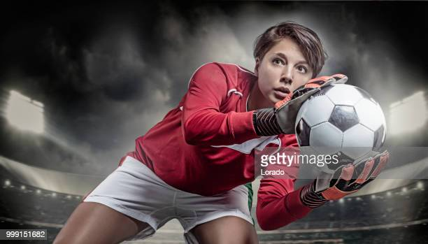 beautiful long haired twenty something soccer player saving a football in a stadium - soccer player stock pictures, royalty-free photos & images