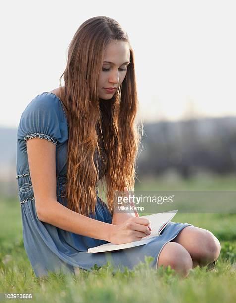 Beautiful long haired woman writing in journal