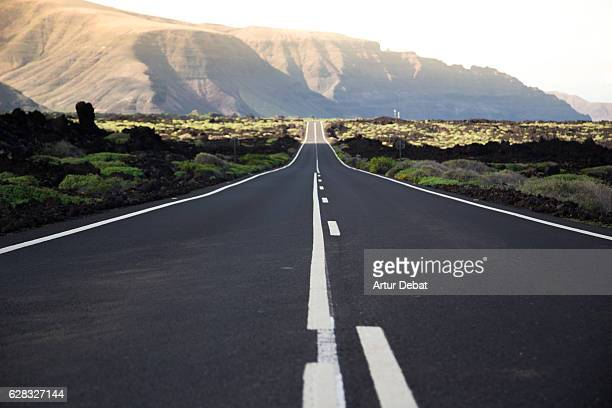 Beautiful long straight road in the volcanic island of Lanzarote during a road trip in a stunning landscape.