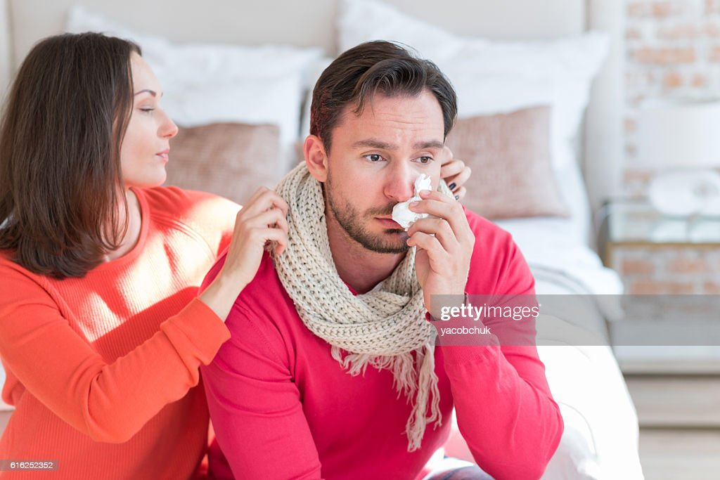 Beautiful loving wife caring about her ill husband : Stock Photo