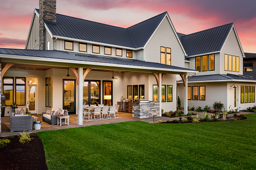 Beautiful luxury home exterior at sunset, featuring large covered patio with outdoor kitchen and barbecue 1208206114