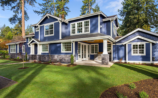 Beautiful luxury home exterior on bright sunny day with green grass and blue sky 968025444