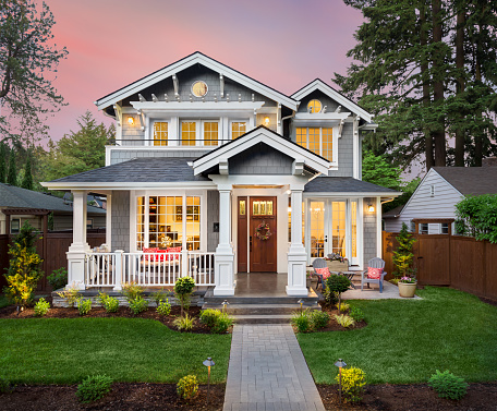 Beautiful luxury home exterior with glowing interior lights at sunset in suburban neighborhood 972895148