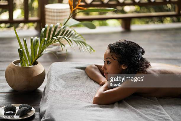 Beautiful Malaysian woman relaxing at the outdoor spa.