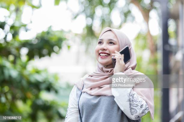 Beautiful Malaysian woman talks on smart phone