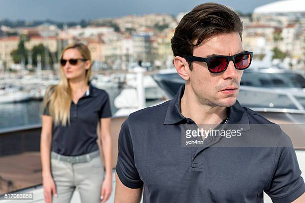 Beautiful man and woman posing on yacht