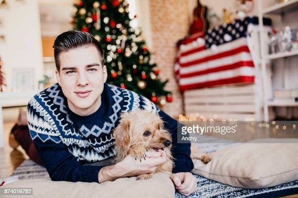 beautiful man holding his dog in front of a christmas tree - happy new month stock photos and pictures