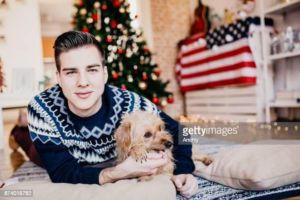 Mooie man met zijn hond voor een kerstboom