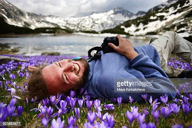 Beautiful man lying on meadow with crocuses