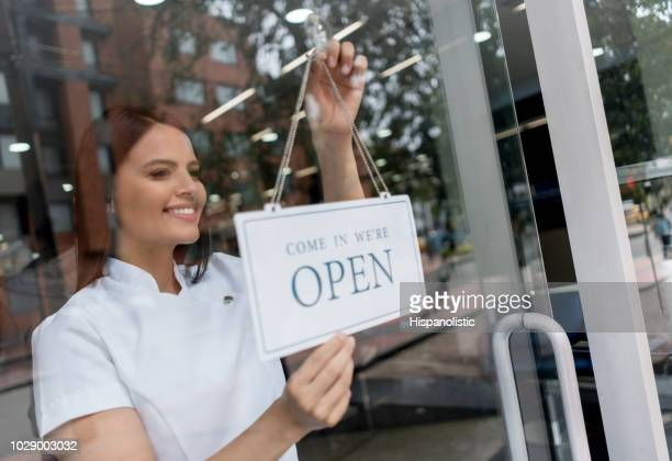 beautiful manager of a hair salon hanging the open sign looking confident and smiling - centro estetico foto e immagini stock