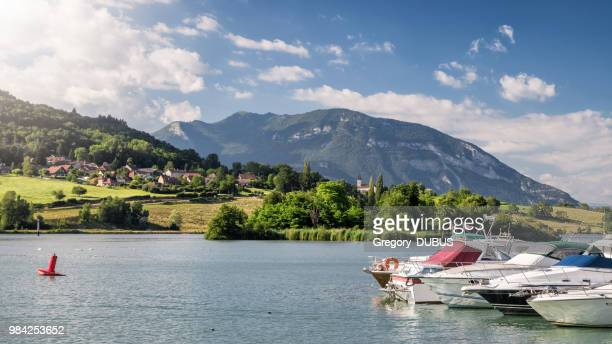 beautiful marina harbor on rhone river with recreational boats with small french village and church in middle of bugey alps mountains - rhone stock pictures, royalty-free photos & images