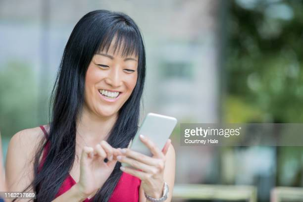 beautiful mature adult japanese woman smiles while using a smart phone to send text message - telephone number stock pictures, royalty-free photos & images