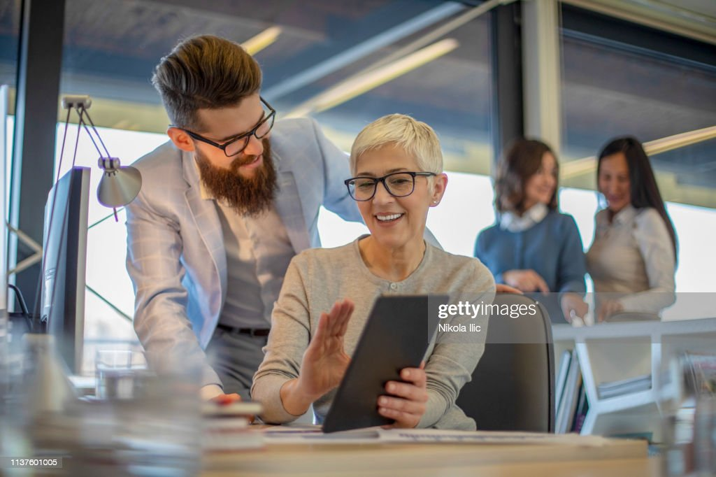 Beautiful mature business woman is talking to a young beard colleague : Stock Photo