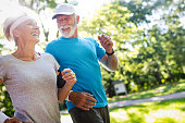 Beautiful mature couple jogging in nature living healthy