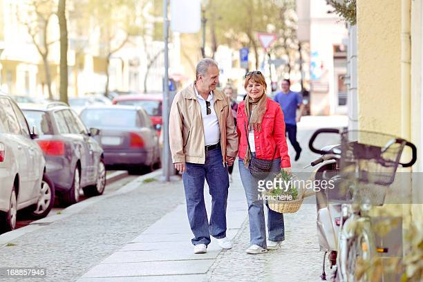 Beautiful mature couple walking home with grocery shopping