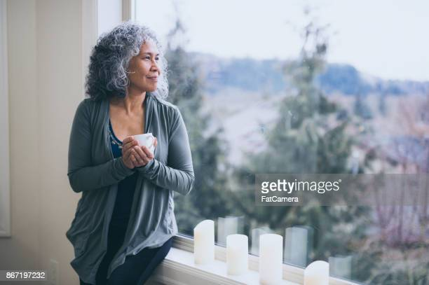 beautiful mature ethnic woman stands by her window in the early morning with a cup of tea and contemplates the day ahead. - mindfulness stock pictures, royalty-free photos & images