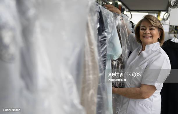 beautiful mature female adult working at a laundry service hanging clothes on conveyor belt while smiling at camera - dry cleaner stock pictures, royalty-free photos & images