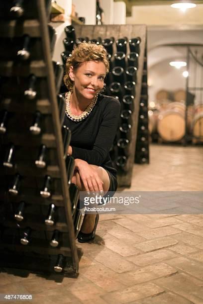 Belle femme d'âge mûr Vintner'vérifiant bouteilles de vin, une cave à vins en Europe