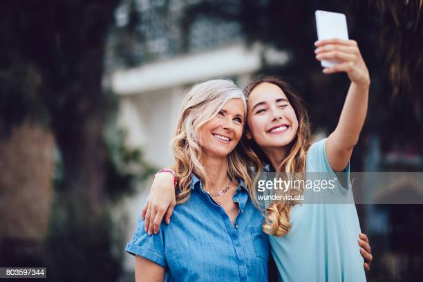 Beautiful mature mother and adult daughter taking selfies together