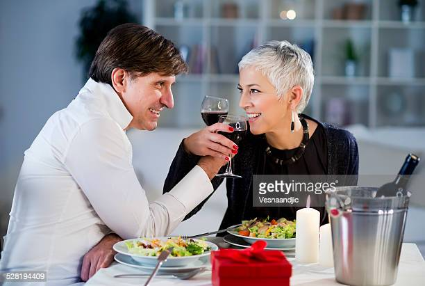 Beautiful mature - senior couple have romantic dinner at home