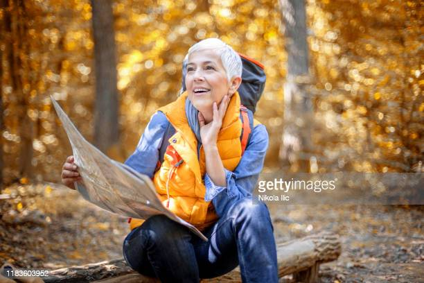 beautiful mature senior women in early 60 hiking in autumn forest - serbia stock pictures, royalty-free photos & images