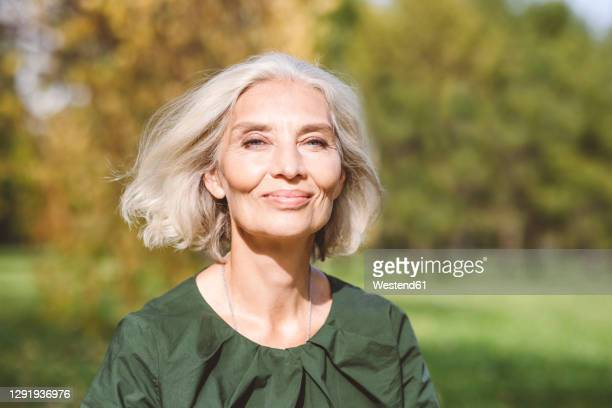 beautiful mature woman at park - hair stock pictures, royalty-free photos & images