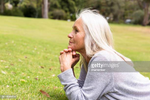 Beautiful mature woman dreaming in the park, copy space