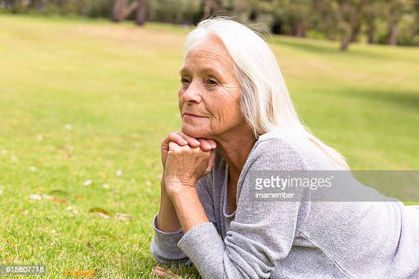 Beautiful mature woman dreaming on the grass, copy space