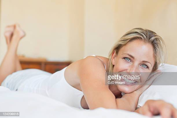 beautiful mature woman lying in bed - pretty older women stock pictures, royalty-free photos & images