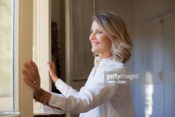 beautiful mature woman opening window - 南ヨーロッパ ストックフォトと画像
