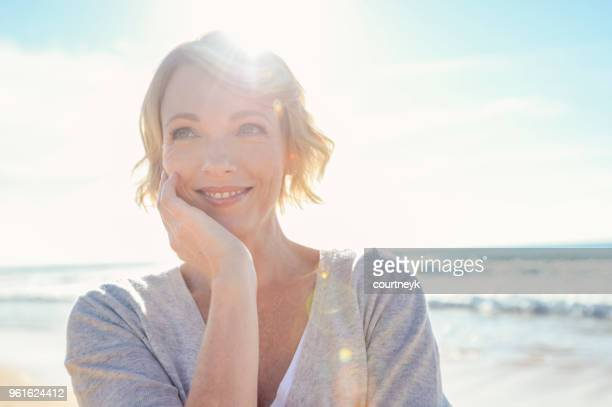 beautiful mature woman portrait on the beach. - lens flare stock pictures, royalty-free photos & images