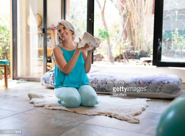beautiful mature woman, prenatal yoga teacher with grey hair - pelvis stock pictures, royalty-free photos & images