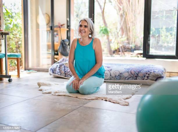 beautiful mature woman, prenatal yoga teacher with grey hair - yoga teacher stock pictures, royalty-free photos & images