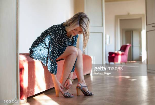 beautiful mature woman putting on shoes - women trying on shoes stock pictures, royalty-free photos & images