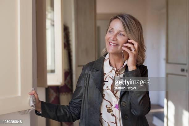 beautiful mature woman ready to leave the house, talking on mobile phone - une seule femme d'âge mûr photos et images de collection