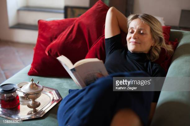 beautiful mature woman relaxing on the sofa with cup of tea and a book - leggere foto e immagini stock