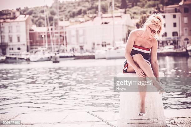 Beautiful mature woman sitting at the sea
