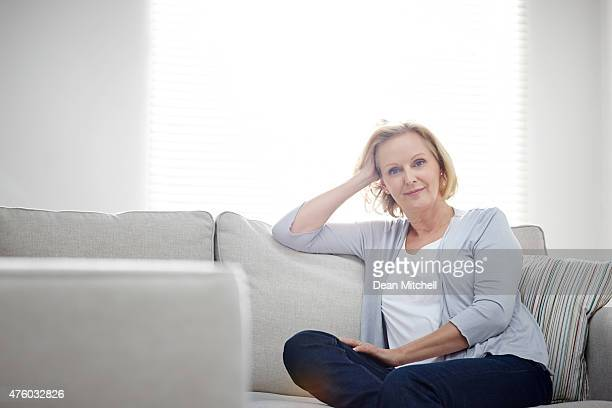 Beautiful mature woman sitting relaxed on a couch