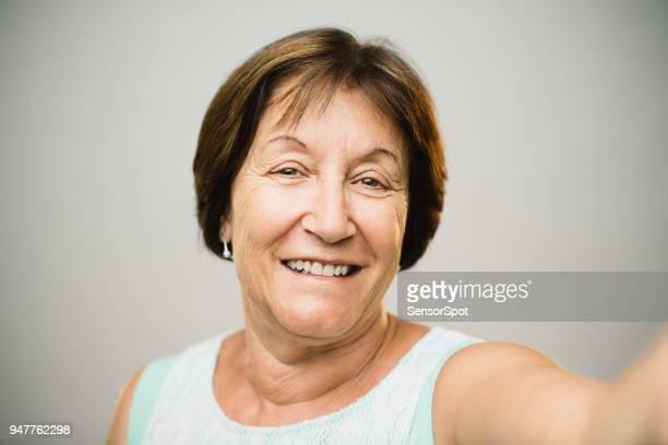 Beautiful mature woman taking selfie