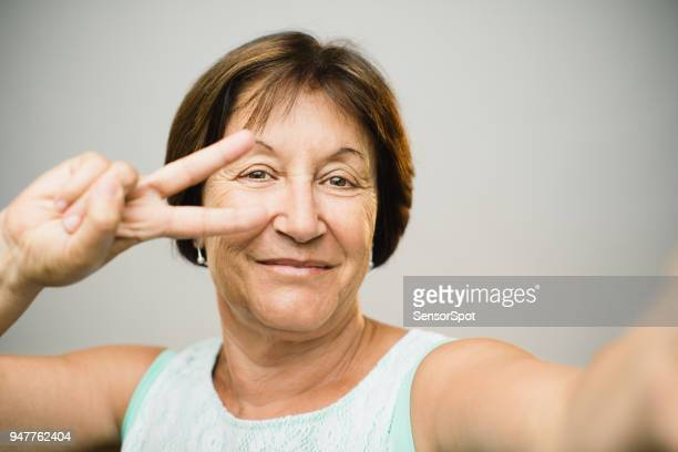Beautiful mature woman taking selfie with peace sign