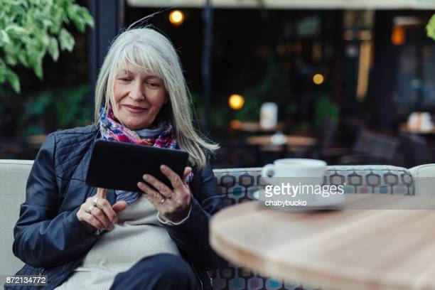 Beautiful mature woman using technology in cafe