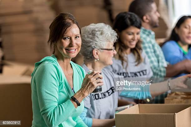 Beautiful mature woman volunteers at food bank