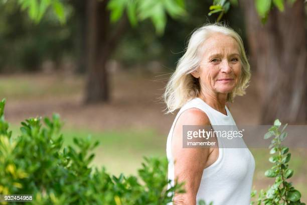 Beautiful mature woman walking in the park, background, copy space