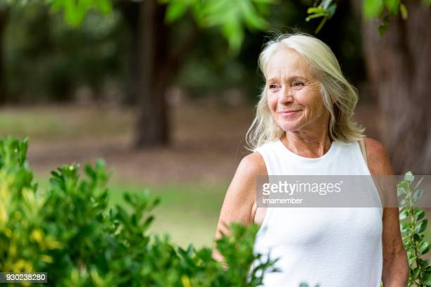 Beautiful mature woman walking in the park, copy space