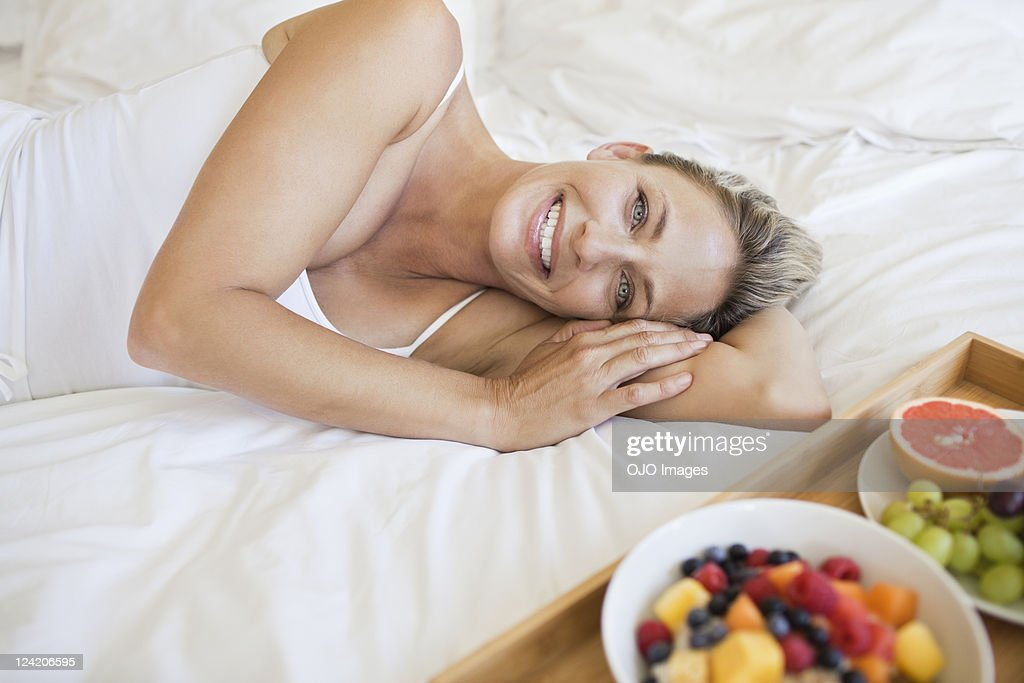 Beautiful mature woman with breakfast on bed : Stock Photo