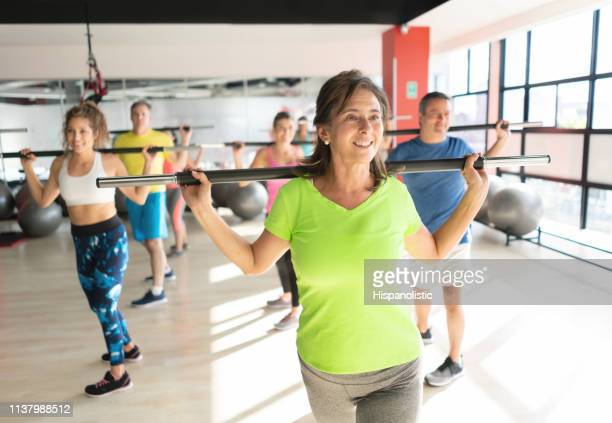 beautiful mature woman working out with gym equipment during class at a health club - hispanolistic stock photos and pictures