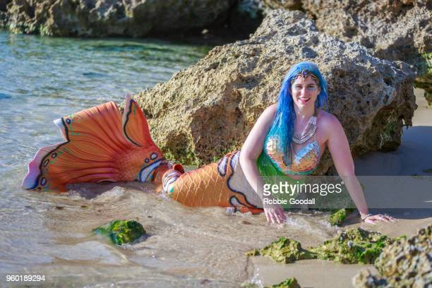 beautiful mermaid with an orange tail and blue hair on a western australian beach. - parte del cuerpo animal fotografías e imágenes de stock